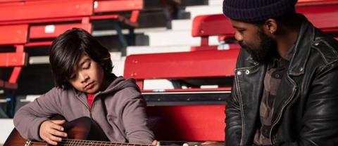 Joe and Larry practice guitar at Yankee stadium.