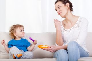 A mom and toddler eat a snack together