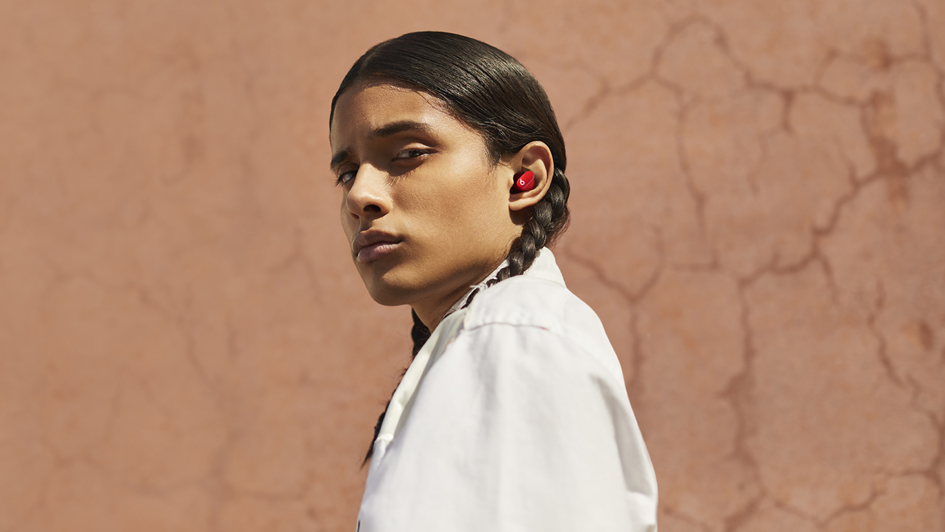 A girl wearing the Beats Studio Buds in red.