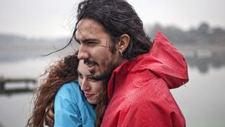 A man and a woman wearing waterproof jackets embrace in the rain