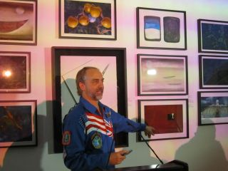 Richard Garriott, an American space tourist and video game developer, stands in front of pieces of art that were displayed on the International Space Station in 2008. The artwork is part of a free exhibit, called Celestial Matters, at the Charles Bank Gal
