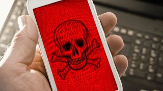 White smartphone displaying skull and crossbones on red screen background.
