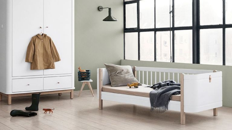 Cuckooland toddler bed – Oliver Furniture Wood Mini+ Kids Junior Bed –inside modern kids bedroom with wooden floor, white walls and black windows with matching wardrobe