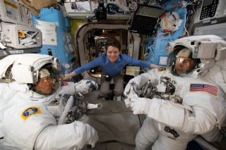 NASA astronaut Anne McClain assists during a spacesuit fit check with Christina Koch (left) and Nick Hague (right).