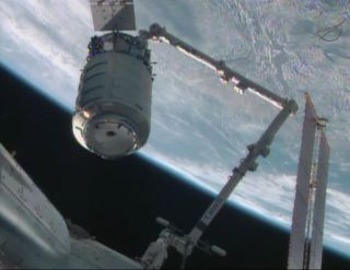 The first commercial Cygnus spacecraft is moved into docking position by the International Space Station's robotic arm on Sept. 29, 2013 after arriving at the orbiting lab during a major test flight by spacecraft builder Orbital Sciences Corp.