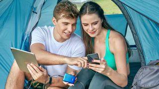 Par i teltåpning med mobile enheter og powerbank.