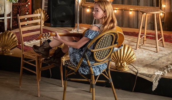Holly Hobbie Holly sits with her guitar, playing