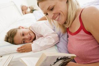 A mom reads a bedtime story to her daughter.