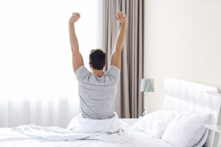 A man stretches when he wakes up in the morning.