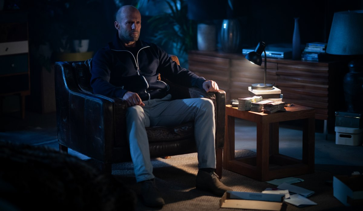 Jason Statham sits in a darkened living room in Wrath of Man.