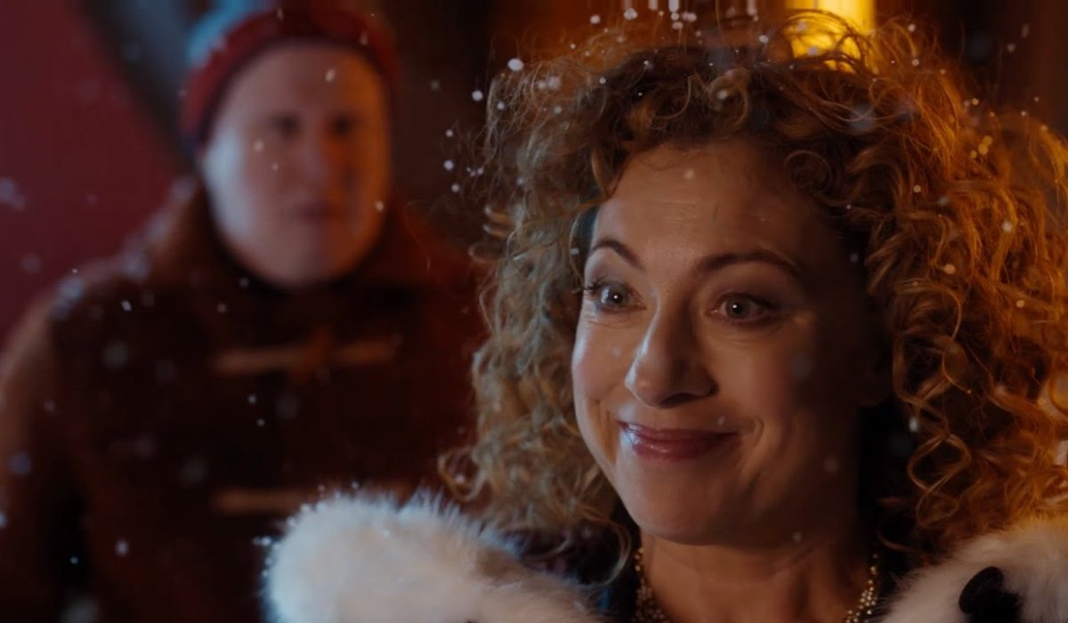 Doctor Who River Song stands in the snow with Nardole behind her
