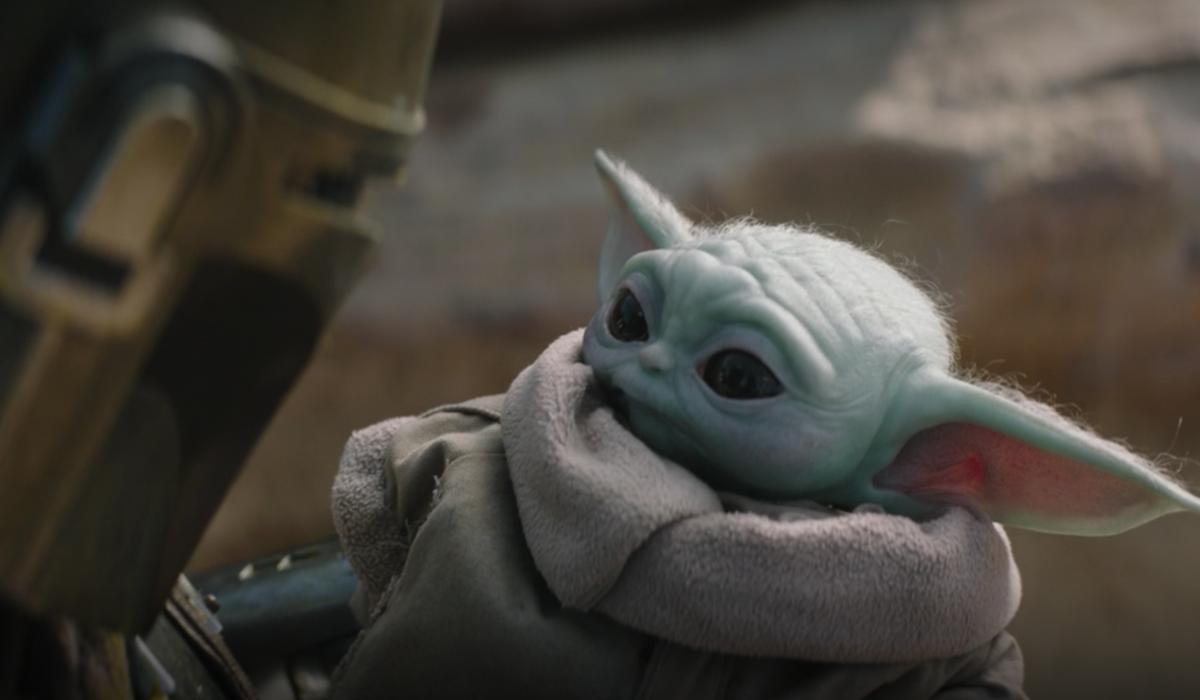 baby yoda held by mandalorian