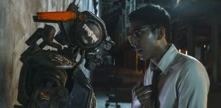 "The ""feeling"" robot Chappie and his maker, Deon, face off in the film."