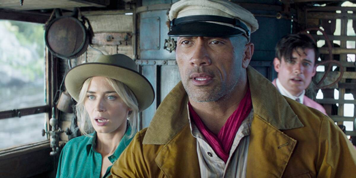 Dr. Lily Houghton (Emily Blunt), Frank Wolff (Dwayne Johnson) and MacGregor Houghton (Jake Whitehall) stand on a boat and look shocked in 'Jungle Cruise'