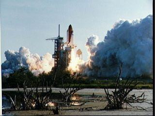 A view of the launch of the shuttle Discovery on its STS-41D mission. The orbiter is seen just leaving Launch Pad 39A with clouds of smoke below it.