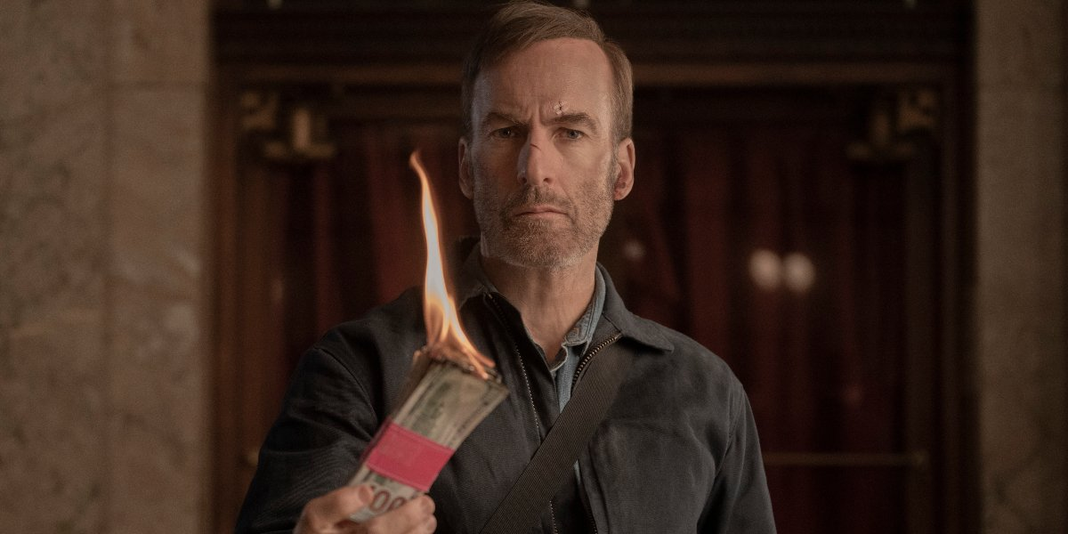 Bob Odenkirk holds some burning money in Nobody.