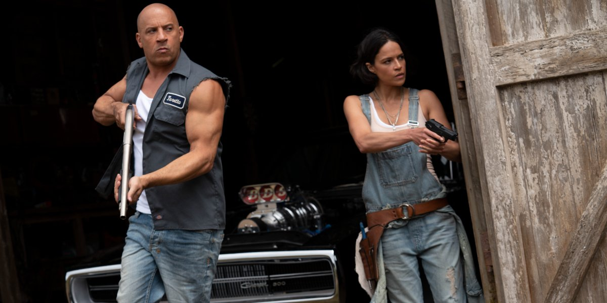 Vin Diesel and Michelle Rodriguez storming out of the barn guns drawn in F9.