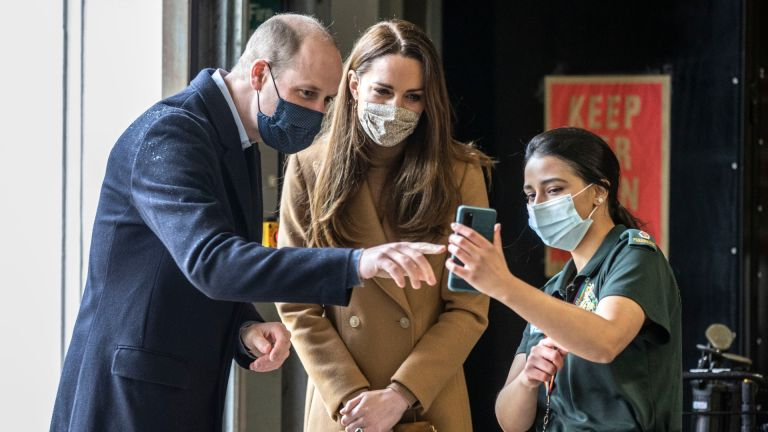 Prince William, Duke of Cambridge and Catherine, Duchess of Cambridge talk with the family of paramedic Jahrin (Jay) Khan via a mobile phone during a visit to Newham ambulance station in East London on March 18, 2021 in London, England