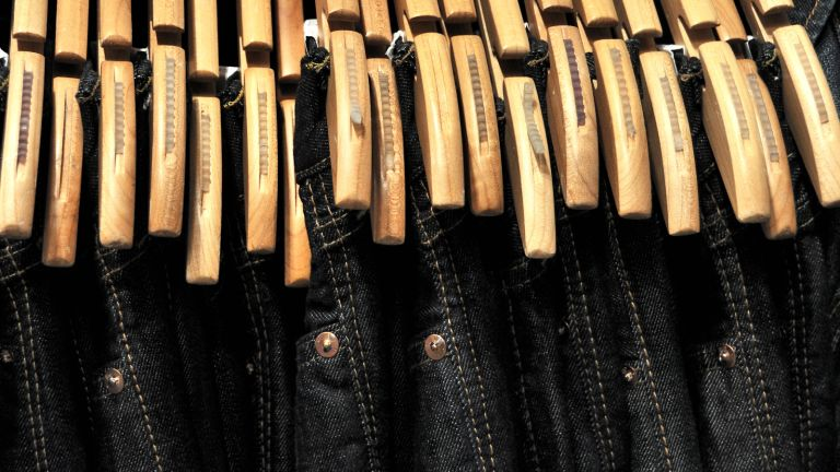 Black jeans lined up with wooden coat hangers – what to wear with black jeans