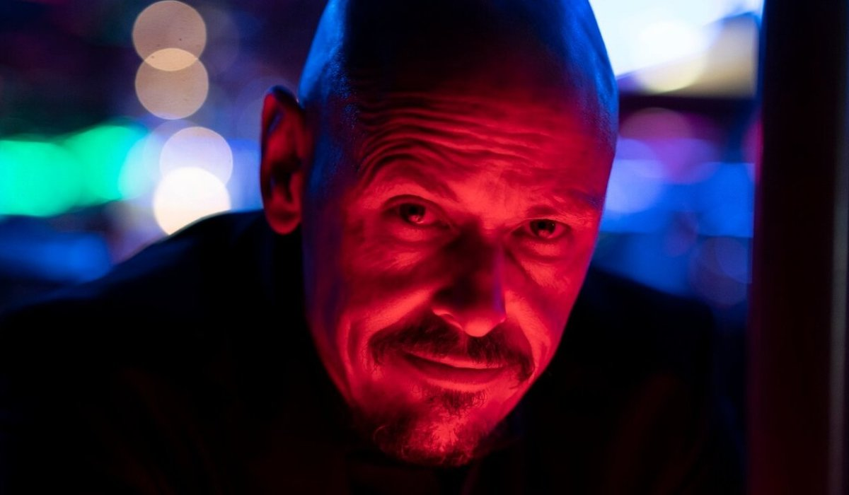 Scott Ryan smiles in a red lit bar in Mr. Inbetween.