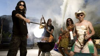 A press shot of Tool posing next to a swimming pool, having a barbecue
