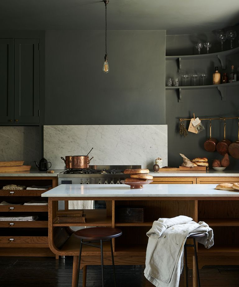 An example of modern kitchen island ideas showing a peninsula with a white worktop and wooden cabinets and shelving next to a range cooker in a kitchen with green walls and ceiling