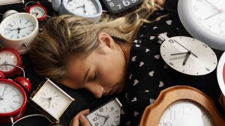 The best times to sleep and wake-up: A woman asleep surrounded by alarm clocks