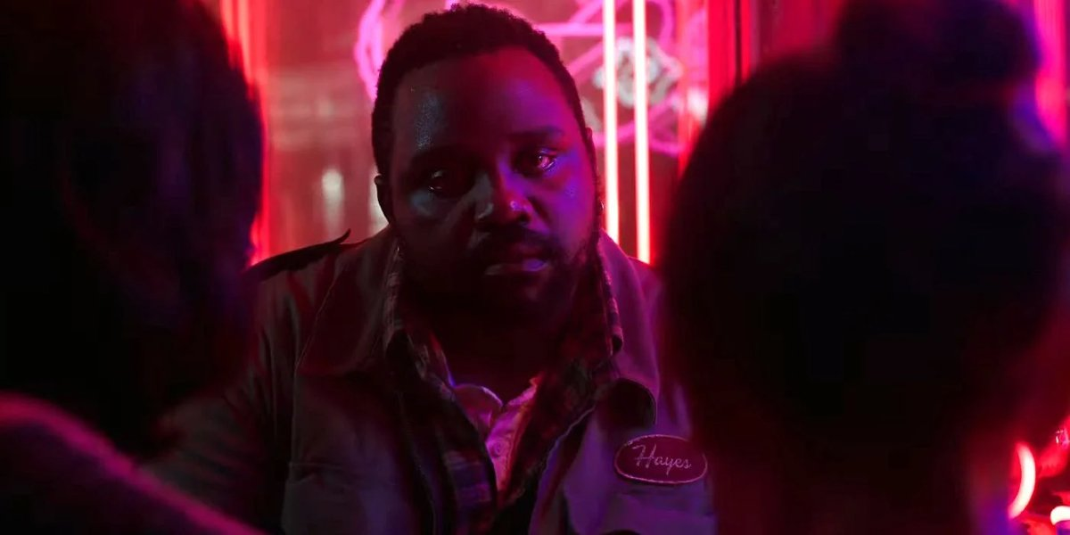 Brian Tyree Henry sitting in a brightly lit restaurant with Julian Dennison and Millie Bobby Brown in Godzilla vs Kong.