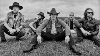 Lukas Nelson & Promise of the Real sitting on grass