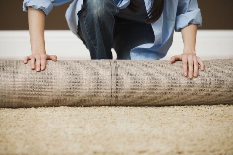 man rolling up carpet