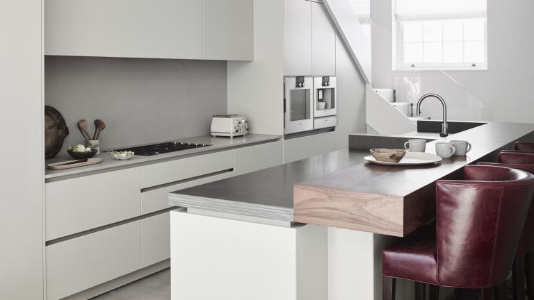 A modern kitchen with white, matt lacquer, handleless cabinetry and black walnut raised breakfast bar