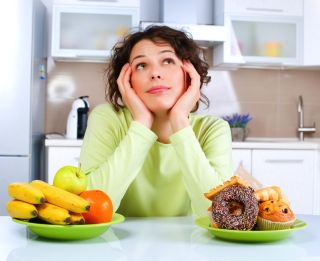 A woman thinks about whether to eat fruit, or donuts.
