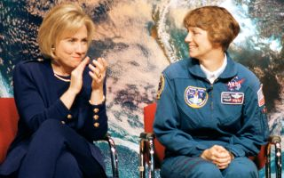 Hillary Clinton applauds now-retired NASA astronaut Eileen Collins, the first woman to command and pilot the space shuttle, during an outreach event at Dunbar High School in Washington, D.C., on March 5, 1998.