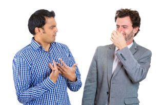 man looking at guy closing, covering nose, something stinks
