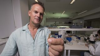 Geoffrey Clark of The Australian National University holds a piece of the 2,700-year-old tattooing kit from Tonga.