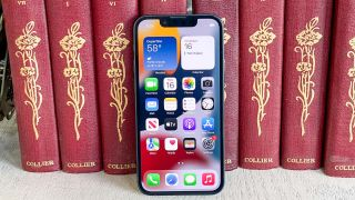 iphone 13 mini display on leaning against books