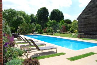 an outdoor swimming pool by a self build house
