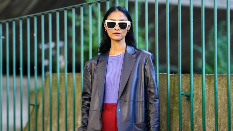 Pornwika Spiecker wears gold earrings, white sunglasses, a purple ribbed t-shirt, a black shiny leather long blazer jacket, high waist red large pants, a burgundy shiny leather large handbag, black and white leather pointed pumps heels shoes, outside the Stella McCartney show, during Paris Fashion Week - Womenswear Spring Summer 2022, on October 04, 2021 in Paris, France.
