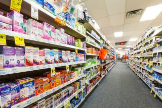 The shelves of a drug store are lined with medicines.