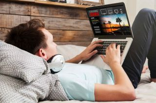 Teen boy with headphones works at laptop computer while lying in bed.