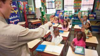 Male teacher points to child raising hand in classroom