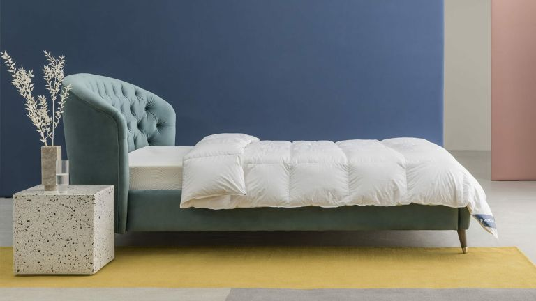 A duvet cover laid on a bed with a teal velvet headboard in a contemporary bedroom