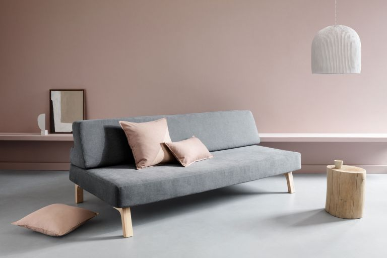Minimalist design with chalky pink wall with floating bench attached, pink chushions and a grey sofa, tree stump coffee table