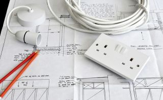 plug socket and cables on top of renovation plans