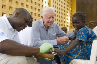 Jimmy Carter comforting girl who has Guinea worm.