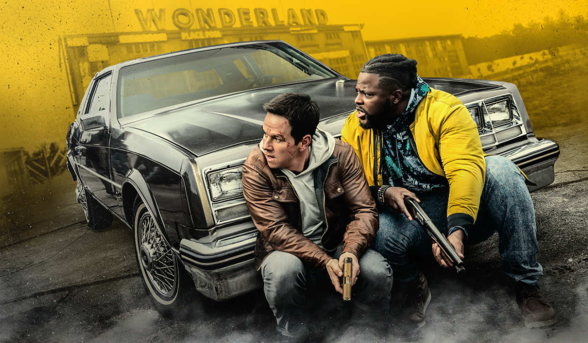 Spenser Confidential Mark Wahlberg and Winston Duke take cover in front of a car