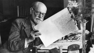 Sigmund Freud, 1856-1939, Austrian psychiatrist, in the office of his Vienna home looking at a manuscript.
