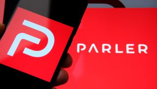 The Parler app's logo displayed on a smartphone screen and what might be a PC.