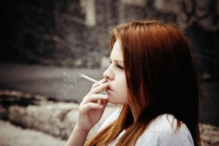 A teenage girl smokes a cigarette.