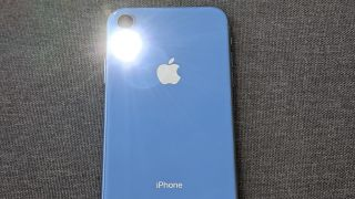 A close-up of an iPhone back with the flashlight on